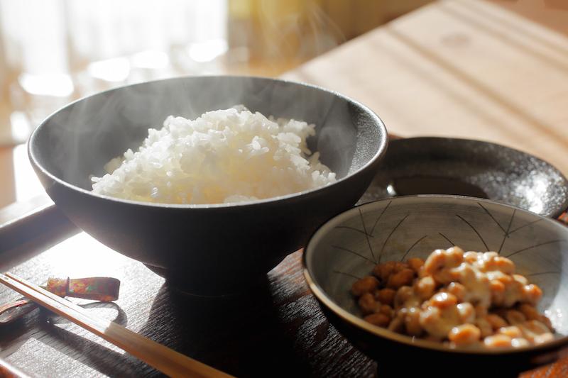 白いご飯、納豆、しょうゆ、箸の置かれたおぼん