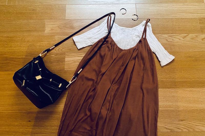 ZARAのストラップリブワンピースのブラウンと白Tシャツとピアスと黒の革バッグ