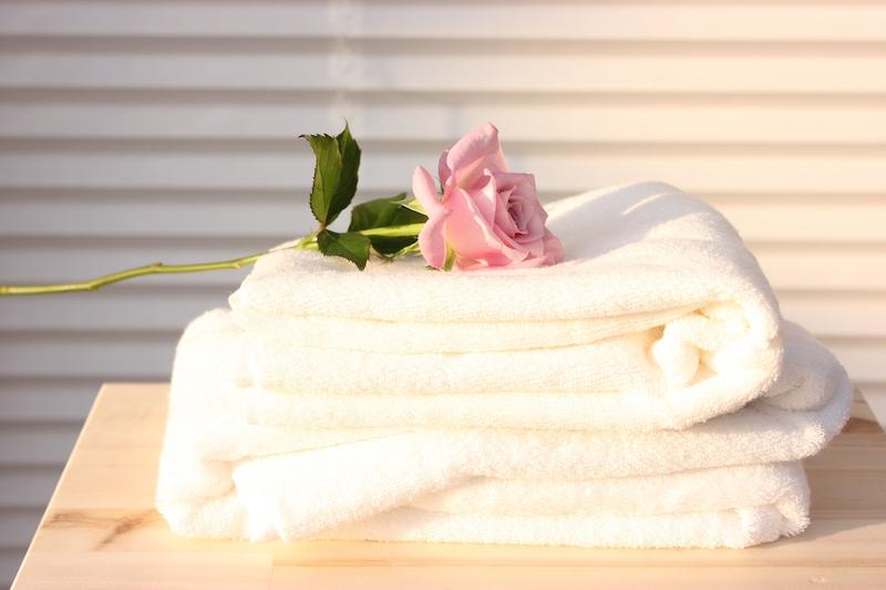 重なったタオルの上にバラが置いてある