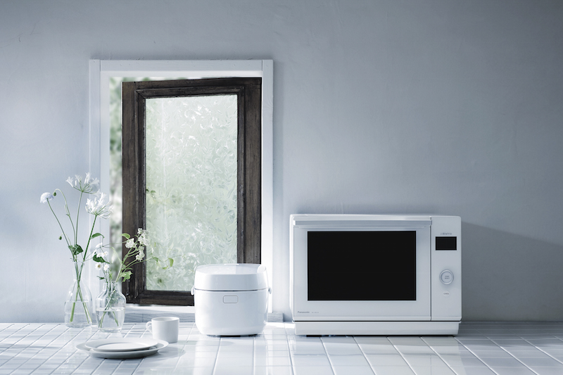 パナソニック 「IHジャー炊飯器 ライス&クッカー SR-UNX101」と電子レンジと花瓶に花がさしてあるキッチンの一角