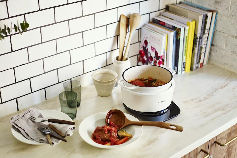 煮込み料理が入った愛知ドビー『バーミキュラ ライスポットミニ RP19A』と取り分けた皿、カトラリーとコップなどが置かれたキッチン