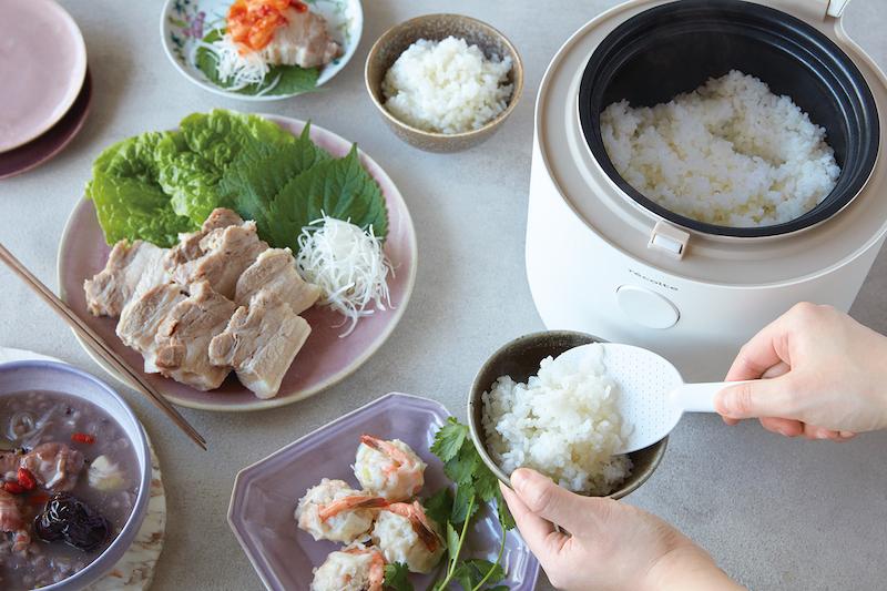 糖質オフ炊飯器からご飯をよそっているところ。周りにはゆで豚などの料理が並ぶ