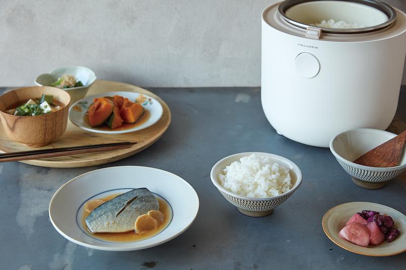レコルトの糖質カット炊飯器の茶碗に盛られたご飯、かぼちゃの煮物、サバの味噌煮、漬物などの皿が周りに並ぶ