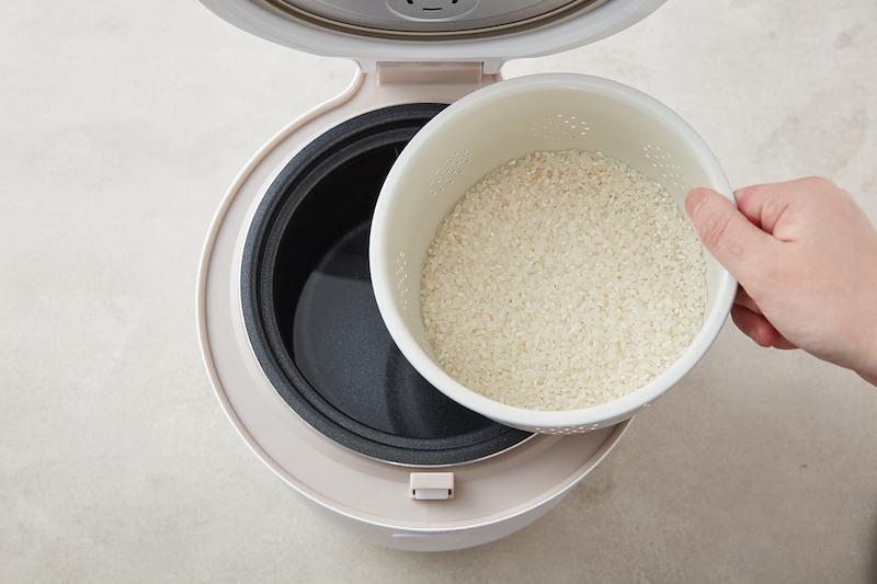 炊飯器に穴の空いたザルのような内釜に入れたお米をセットしようとしている