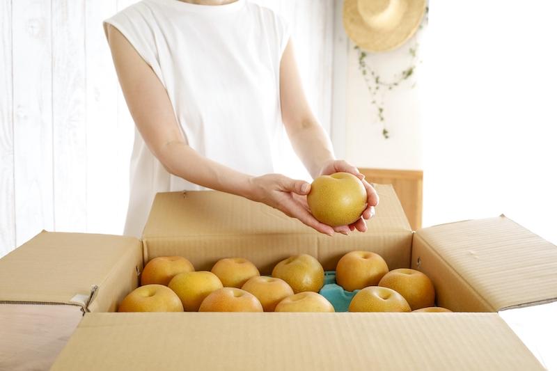 箱から梨を取り出す人